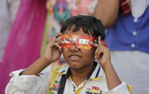 A boy looks at the sun in Lucknow, India