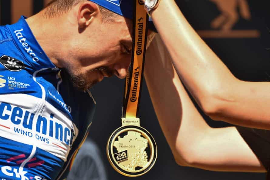 Stage 13 winner France's Julian Alaphilippe receives a medal as he celebrates his victory on the podium after the individual time trial over 27.2 kilometers with start and finish in Pau.