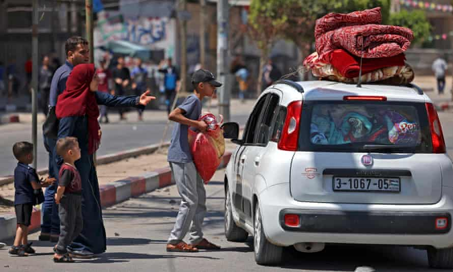 A Palestinian family flees with their belongings stacked on top of a car in Beit Hanun in the northern Gaza Strip