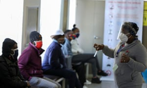 A medical worker talks to volunteers as they wait to receive an injection during the country's first human clinical trial for a potential vaccine against the novel coronavirus, in Soweto, Johannesburg, South Africa.