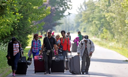 Three families from Burundi cross into Quebec at the US-Canada border from Champlain, New York on 3 August 2017.