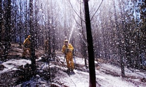 A firefighter sprays foam onto an area hit by bushfires at Ballarat in Victoria in 2000.