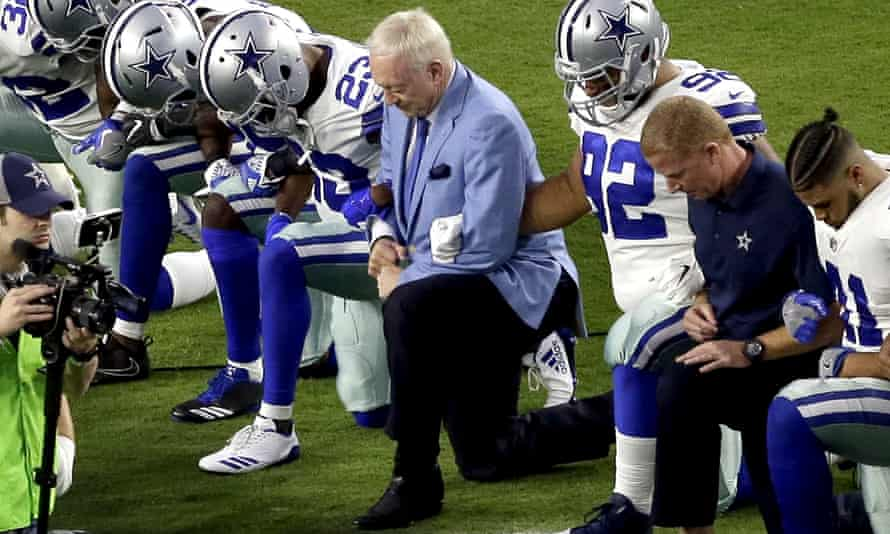 Dallas Cowboys Jerry Jones, center, initially took part in the NFL player protests but says his team must now stand for the anthem