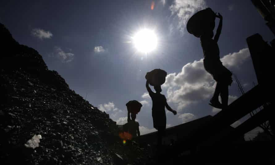 Labourers carry coal to load on a truck in Gauhati, India