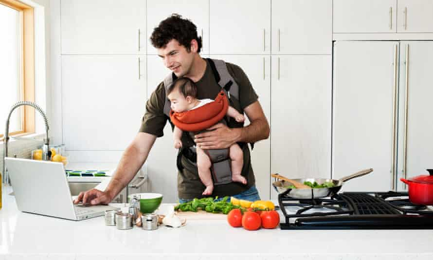 A man cooking while carrying a baby in a sling: is this macho enough for you or nah?
