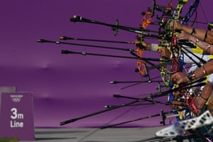 Tokyo, Japan. Archers hold their bows during a day of ranking at Yumenoshima archery field, ahead of the start of the Tokyo Olympics