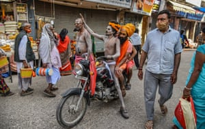 Indian holy men travel by motorbike to take a holy dip in the Ganges River during the Kumbh Mela, Haridwar
