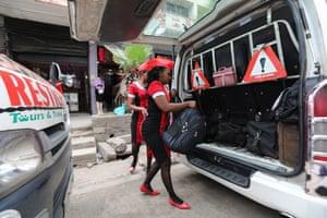 A matatu conductor loads bags into a van travelling from Nakuru to Nairobi
