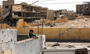 A Syrian Democratic Forces fighter seen at a temporary SDF base, overlooking a cemetery that was destroyed during heavy clashes with ISIS militants.