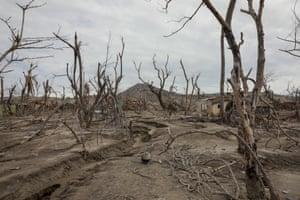 Damaged houses among ash deposits