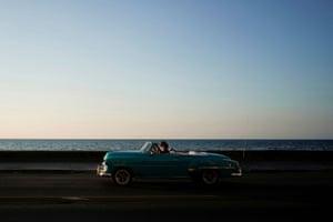 Havana, Cuba People wear protective masks as they ride in a vintage car in Havana