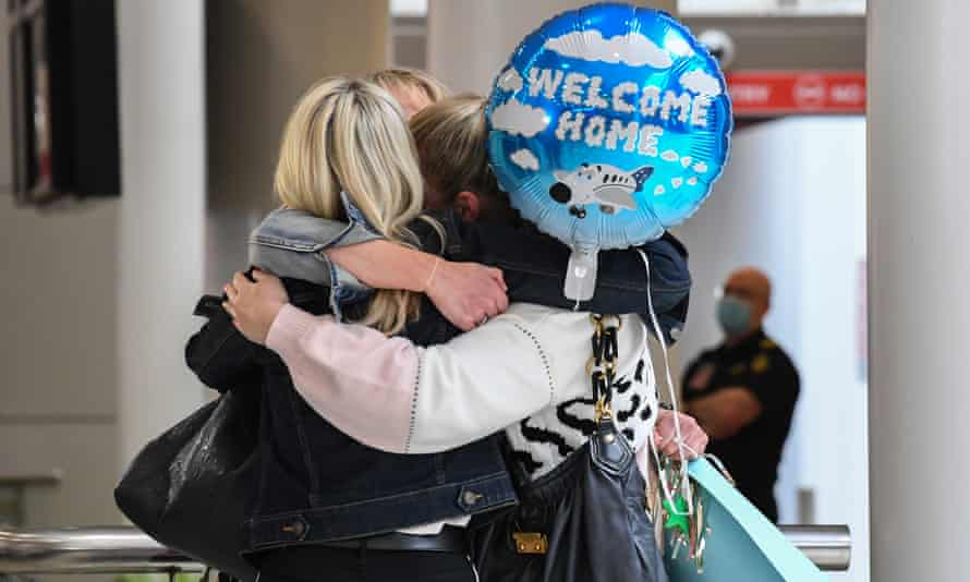Friends hug one another as they arrive at Sydney's Kingsford Smith Airport after landing on Air New Zealand flight
