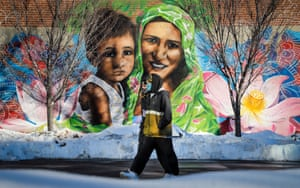 A couple wearing masks walk past a mural of a mother and child in Calgary, Canada