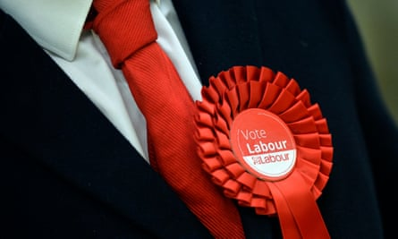 A Labour supporter wears a rosette in support of the party