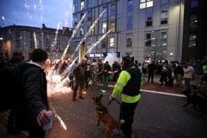 Fireworks are launched as police officers with dogs arrive.