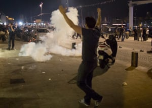 A man walks toward teargas fired by police, following scuffles in Marseille.