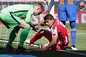 Barcelona's goalkeeper Marc-Andre ter Stegen, left, helps Atletico Madrid's Luis Suarez.