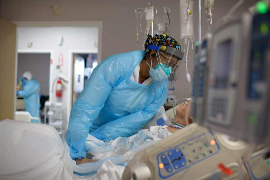 Demetra Ranson, a healthcare worker, comforts a patient in the Covid-19 ward at United Memorial medical center in Houston on 4 December.