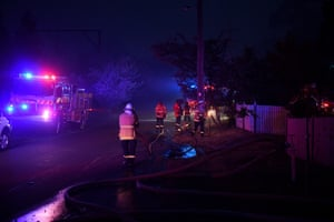 NSW Rural Fire Service and Fire and Rescue NSW personnel conduct property protection on Railway Parade in Woodford