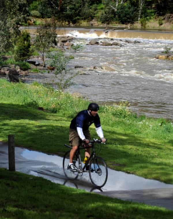 A cyclist rides along the Yarra River near Dights Falls in Collingwood.