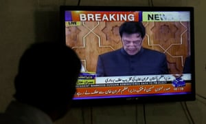 A man looks at a television screen displaying cricketer-turned-politician Imran Khan's swearing in as prime minister of Pakistan.