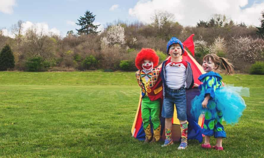 Three smiling children dressed as clowns