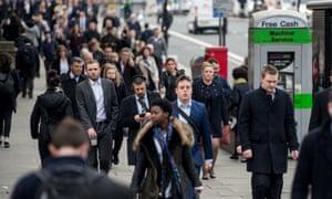 Commuters walk over London Bridge in central London