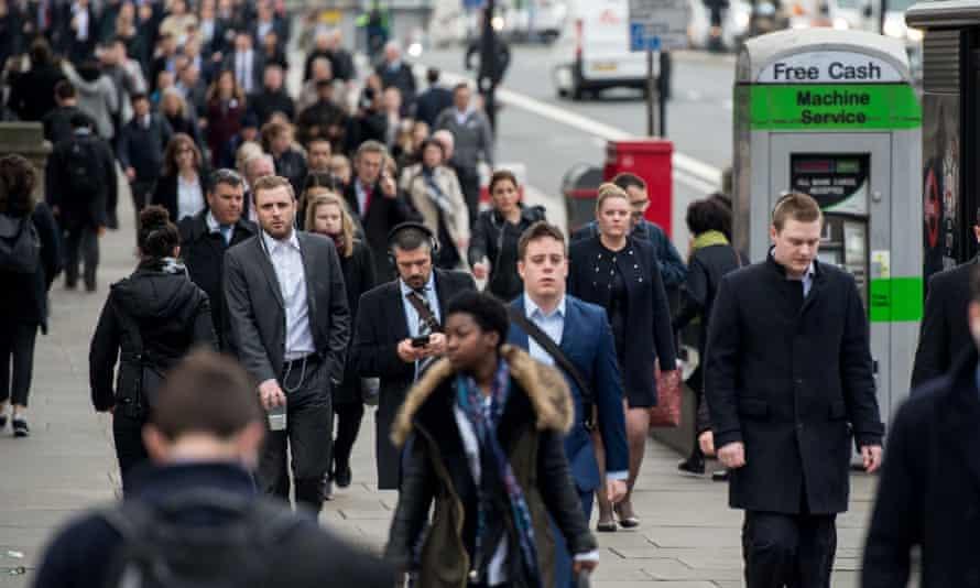 Commuters walk over London Bridge