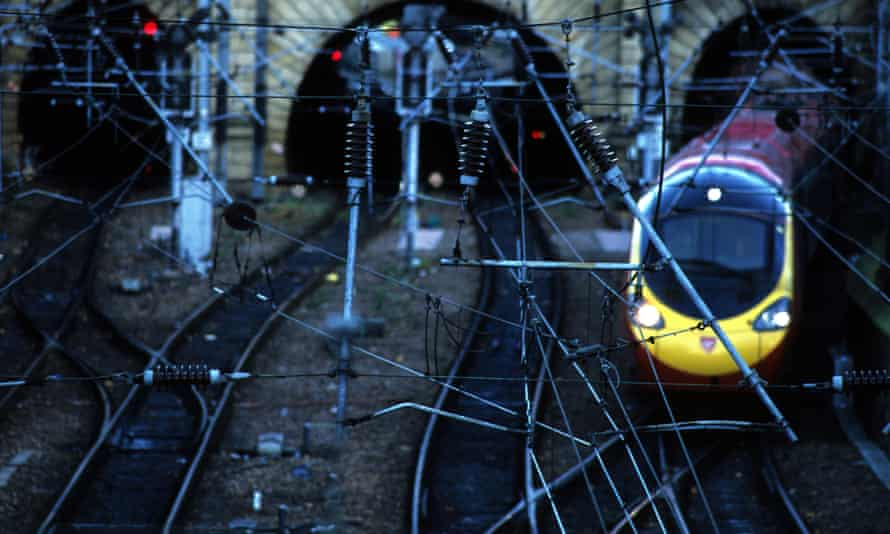 train on track with lots of electricity wires overhead