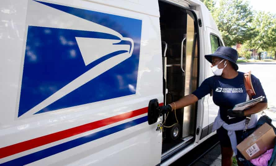 A mail carrier of the United States Post Office (USPS) delivers mail.