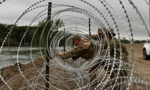 Soldiers install barbed wire fences on the banks of the Rio Grande in Laredo, Texas on 18 November.