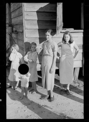 black and white photo of family, with large black circle obscuring face of a child