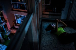 A teenager looks at a smartphone while laying on the floor of her home