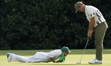 Paul Casey works on his grip while Patrick Reed's caddie, Kessler Karain, lines up a putt for his man on the 5th green.