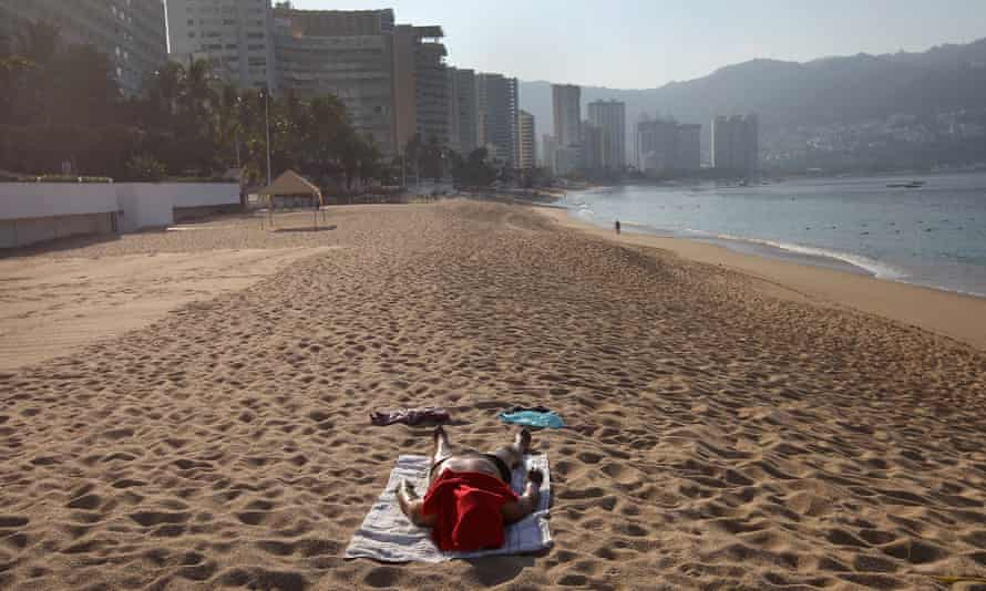 A lone tourist lies out on the beach