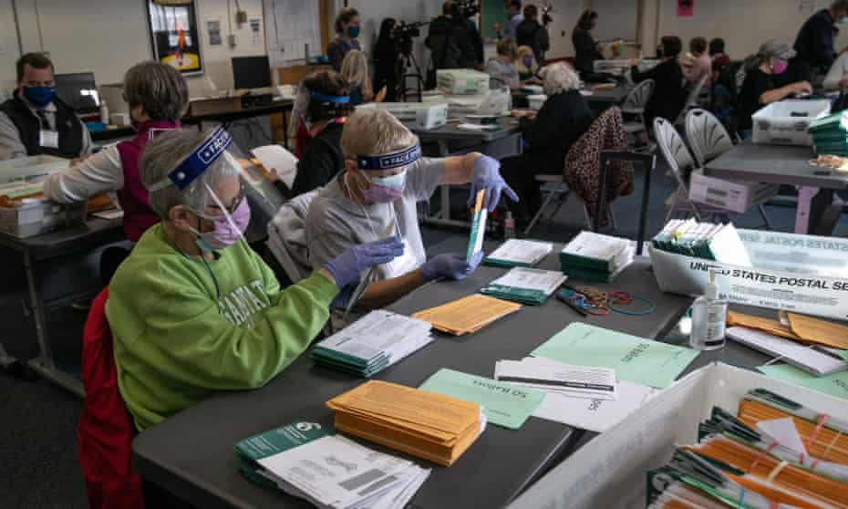 Election workers sort absentee ballot envelopes at the Lansing city clerk's office in Michigan on Monday.