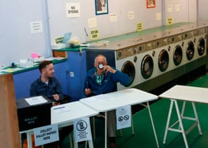 A new spin on polling stations: a presiding officer and a poll clerk wait for early morning voters at a polling station set up in a launderette and nail bar in Headington in Oxford.