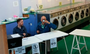 A presiding officer and a clerk wait for voters at a polling station set up in a launderette in Headington, Oxfordshire, on 8 June.