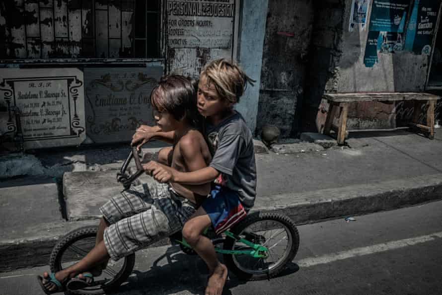 Young boys ride a bicycle past a tombstone engraving shop on our way back again to the Navotas City Jail