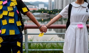 Students put memos on their uniforms as they take part in a human chain event in Sha Tin district in Hong Kong