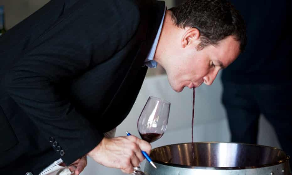 An expert spits out wine