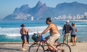 Residents of Rio de Janeiro break social isolation and walk along the beach on 31 May.