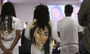 People stand during the funeral for Nia Wilson.