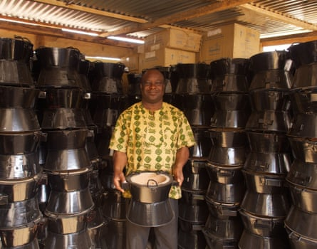Atsu poses with a cookstove in the storeroom of Gyapa Enterprises