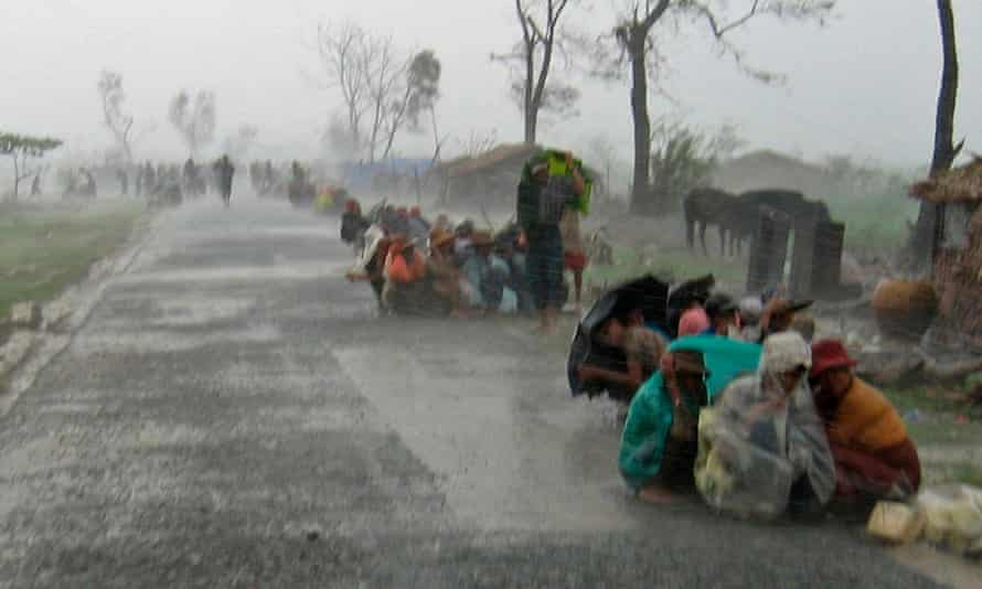 Cyclone victims in Myanmar huddle in torrential rain as they await assistance after Cyclone Nargis