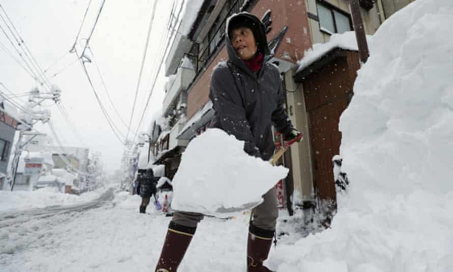 A woman removes snow on a street in Yuzawa, Niigata prefecture.