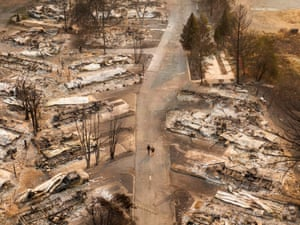 In this aerial view from a drone, people walk through a mobile home park destroyed by fire on 10 September in Phoenix, Oregon. Hundreds of homes in the town have been lost due to wildfire.