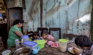 "Consuelo Pascacio's three children; Estiben 4, Estefany, 11, and Javier, 14, dig into a chicken rice stew she picked up at a ""community pot,"" in their home in the Nueva Esperanza neighborhood of Lima, Peru, on Monday, 8 June, 2020. For many residents the ""community pot"" is their only defense against a hunger that's become a constant feature of life amid the new coronavirus pandemic."