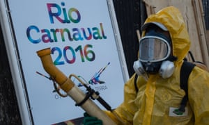 A person in a yellow biohazard suit, with gas mask, holds a long pipe-like fumigator, in front of a poster reading 'Rio Carnaval 2016'.