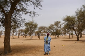 A Droum resident with the village's mature gao trees.